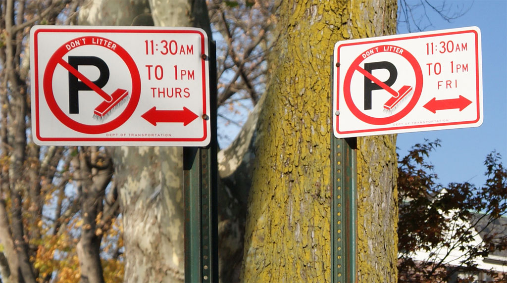 A pair of no-parking-during-street-sweeping-time signs.